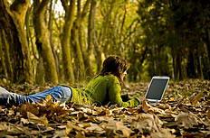 爬在落叶上玩电脑的美女唯美图片