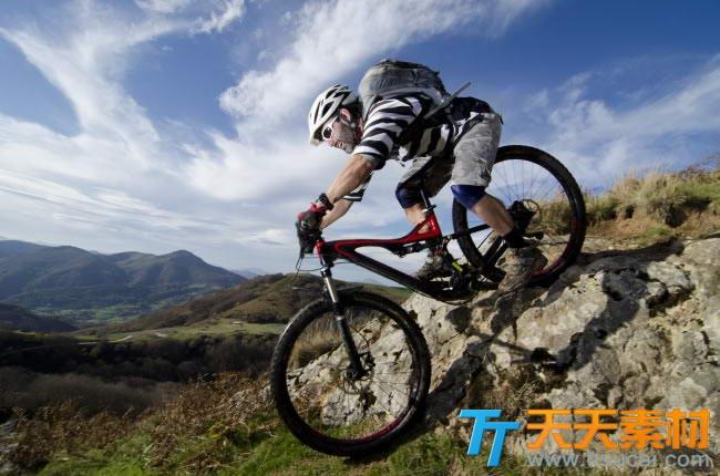 在户外骑山地自行车的背包客图片